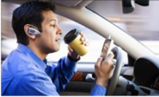 Man driving while drinking coffee and using phone.
